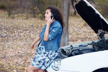 broken telephone: Woman with broken car talk on phone with hood up