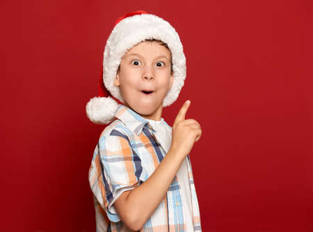 santa helper: winter holiday christmas concept - boy in santa helper hat have idea on red background
