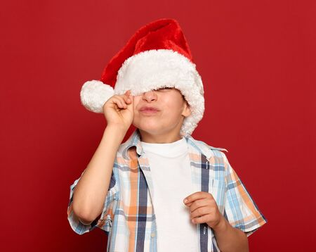 one eye: winter holiday christmas concept - boy in santa hat close one eye on red background
