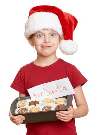 oneself: girl in santa hat with cookies lick oneself - winter holiday christmas concept Stock Photo