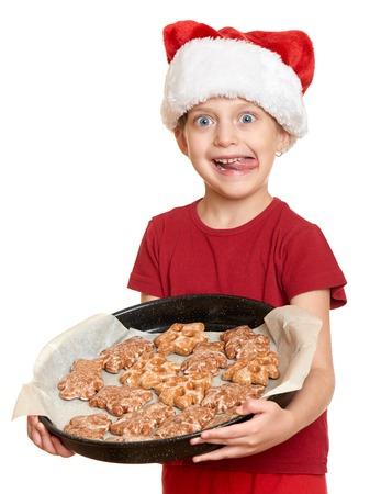 galletas de navidad: chica en el sombrero de santa comer galletas y lamer a sí mismo - el concepto de vacaciones de Navidad de invierno Foto de archivo