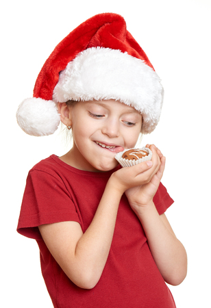 oneself: girl in santa hat eat cookies and lick oneself - winter holiday christmas concept