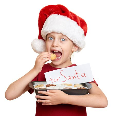 smiling faces: girl in santa hat eat cookies - winter holiday christmas concept Stock Photo