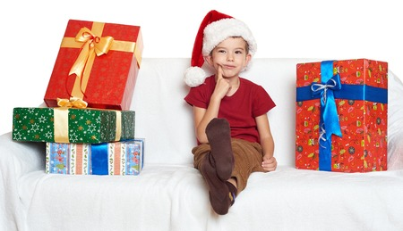 make a gift: boy in red santa helper hat with gift boxes make a wish - christmas holiday concept Stock Photo