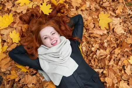 face in tree bark: redhead girl lying on leaves and wink in city park, fall season Stock Photo