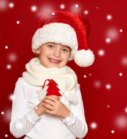 seasonal clothes: winter, child,  christmas concept - happy girl in santa hat show fir tree wool toy on red background Stock Photo