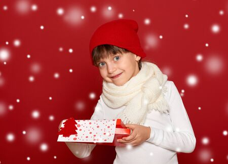 sweater girl: winter, child,  christmas concept - happy girl in hat with box gift show fir tree wool toy on red background