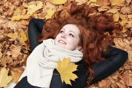lying on leaves: redhead girl lying on leaves in city park, fall season Stock Photo
