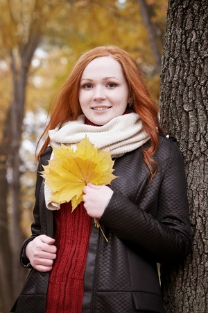 face in tree bark: redhead girl with leaf in city park, fall season