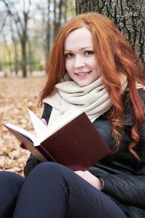 face in tree bark: redhead girl read book in city park, fall season