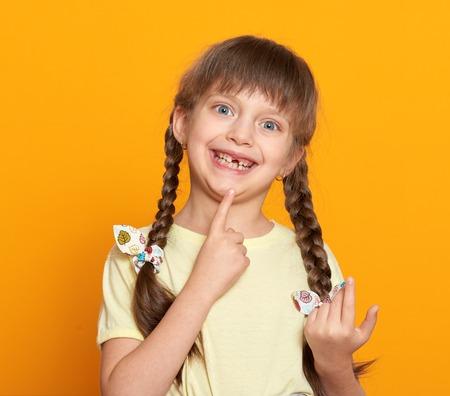 niños riendose: Retrato de la chica diente perdido, estudio disparar sobre fondo amarillo