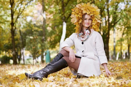 sitting on the ground: girl sitting on leaves in sunny autumn city park