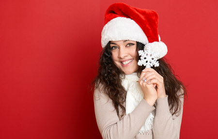 long hair: beautiful young woman portrait in santa helper hat with big snowflake posing on red