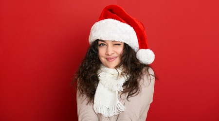 squint: beautiful young woman wink, portrait in santa helper hat and posing on red Stock Photo