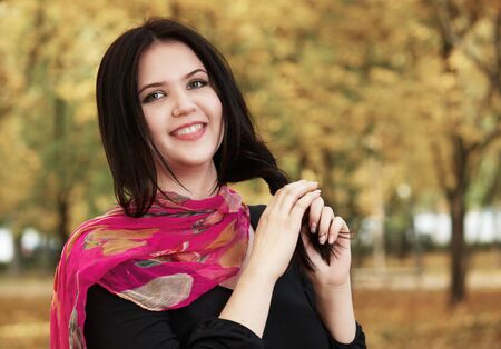 beauty full: beautiful girl in black dress and red scarf in yellow city park, fall