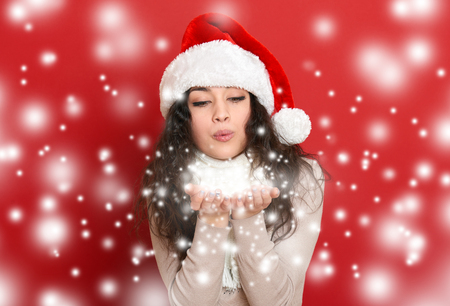 santa helper: beautiful young woman in santa helper hat blowing snow from palms, red background