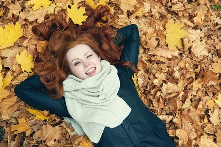wink: redhead girl lying on leaves and wink in city park, fall season Stock Photo