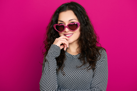 flirtation: beautiful girl glamour portrait on pink in heart shape sunglasses, long curly hair