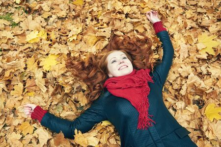 face in tree bark: redhead girl lying on leaves in city park, fall season Stock Photo