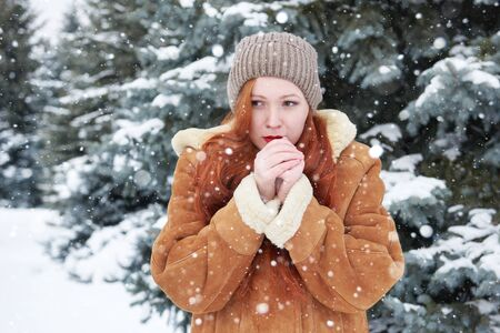 warms: Young woman warms hands at winter, snowy fir trees background