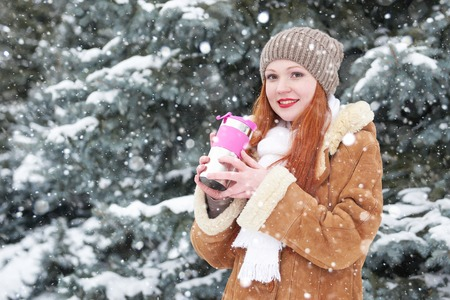 to get warm: Girl drink tea in winter forest at day. Fir trees with snow.