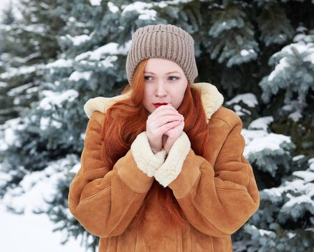 warms: Young woman warms hands at winter outdoor, snowy fir trees background