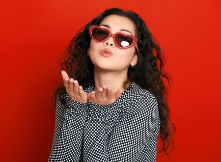 air kiss: beautiful girl glamour portrait on red make flying kiss