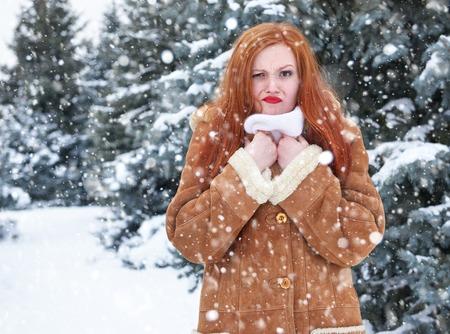 bad hair day: Grimacing woman having discomfort on winter weather, outdoor portrait