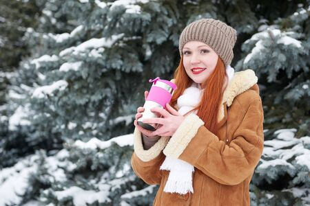 to get warm: Girl get warm and drink tea in winter forest at day. Fir trees with snow.