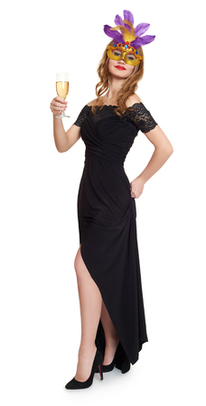 evening gown: Young woman in black evening gown on white. Carnival mask on face. Wineglass champagne in hands.