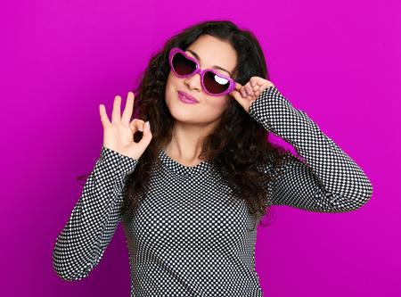 mooie glamour meisje staand op een paars in hartvorm zonnebril, lang krullend haar