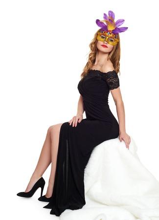 black girl: Junge Frau im schwarzen Abendkleid und Karneval Maske. Setzen Sie sich auf wei�es Fell. Urlaub und Party-Konzept.
