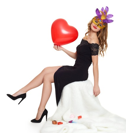 girl portrait: Young woman in black evening gown and carnival mask. Sit on white fur. Heart shaped balloon in hand. Valentine concept.