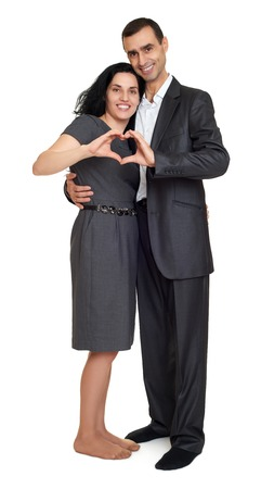 femme romantique: Happy couple dressed in strong classic dress, making heart shape from fingers, studio portrait on white