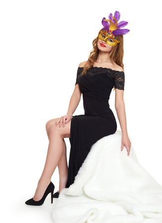 beauty full: Young woman in black evening gown and carnival mask. Sit on white fur. Holiday and party concept.