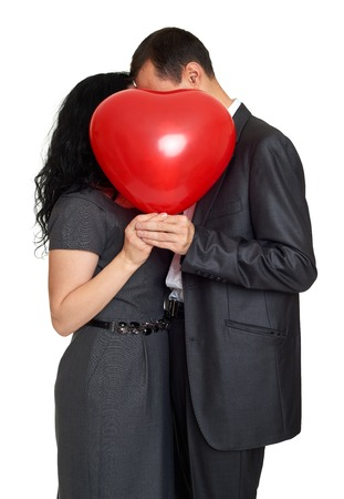 relationship love: Happy couple kissing and hiding behind red heart shaped balloon. Valentine holiday concept. Studio isolated
