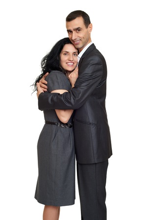grey background: Happy couple embrace, dressed in strong classic dress, studio portrait on white Stock Photo