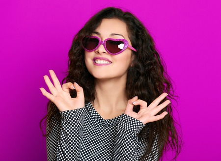 hair studio: beautiful girl glamour portrait on magenta show okay gesture Stock Photo