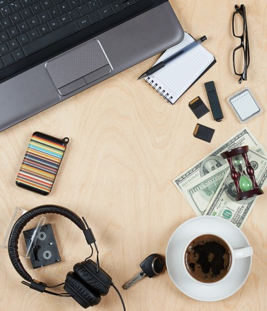blank center: Flat lay of personal stuff, notebook computer,cards, coffee, money and other. Flat design and top view on desk as frame with blank center on wood background.