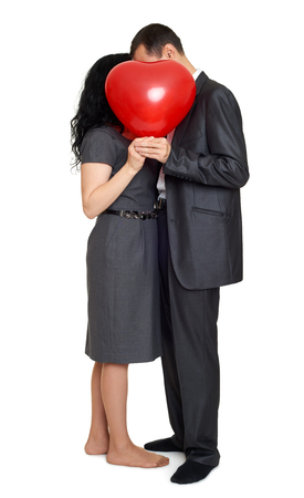 mujer enamorada: Happy couple kissing and hiding behind red heart shaped balloon. Valentine holiday concept. Studio isolated