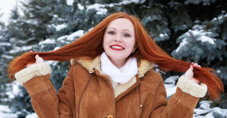 long red hair: Winter woman outdoor portrait show long red hair, snowy fir trees background