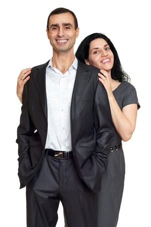 grey background: Couple embrace, studio portrait on white. Dressed in black suit.
