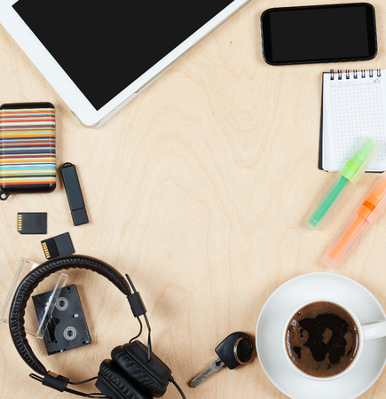 blank center: Flat lay office tools and supplies, tablet computer,cards, coffee and other stuff. Flat design and top view on desk as frame with blank center on wood background. Stock Photo