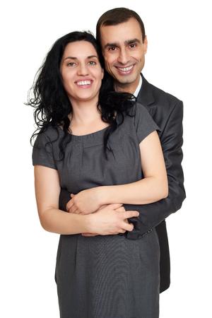 marido y mujer: abrazo pareja, retrato de estudio en blanco. Vestido de traje negro. Foto de archivo