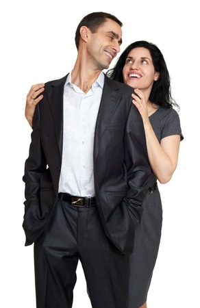 adult family: Couple embrace, studio portrait on white. Dressed in black suit.