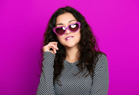 hair studio: beautiful girl glamour portrait on purple in heart shape sunglasses, long curly hair