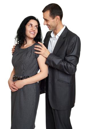 parejas romanticas: abrazo pareja, retrato de estudio en blanco. Vestido de traje negro. Foto de archivo