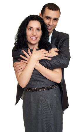 guy portrait: Couple embrace, studio portrait on white. Dressed in black suit.