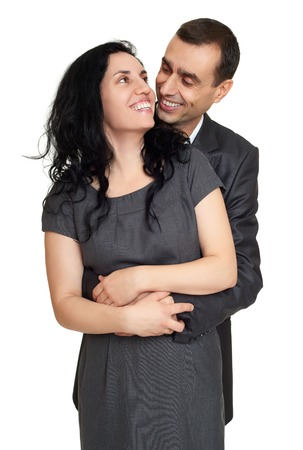 studio background: Couple embrace, studio portrait on white. Dressed in black suit.