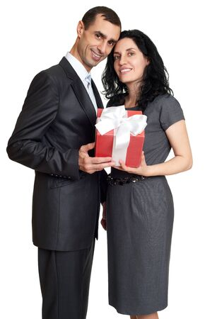 Portrait couple: Couple with gift box, studio portrait on white. Dressed in black suit.